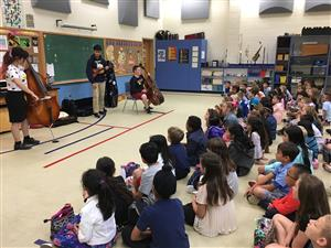 High school students demonstrate string instruments